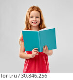 smiling red haired girl reading book. Стоковое фото, фотограф Syda Productions / Фотобанк Лори