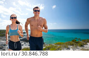 Купить «couple in sports clothes running along on beach», фото № 30846788, снято 1 августа 2018 г. (c) Syda Productions / Фотобанк Лори