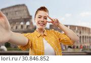 Купить «redhead teenage girl taking selfie over coliseum», фото № 30846852, снято 28 февраля 2019 г. (c) Syda Productions / Фотобанк Лори