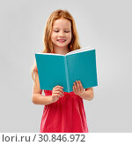 Купить «smiling red haired girl reading book», фото № 30846972, снято 9 марта 2019 г. (c) Syda Productions / Фотобанк Лори