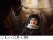 Teenage girl standing near black horse in a stable. Стоковое фото, фотограф Julia Shepeleva / Фотобанк Лори