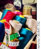 Купить «Coil threads for overlock and measuring tape on serger background», фото № 30847732, снято 18 мая 2019 г. (c) Gennadiy Poznyakov / Фотобанк Лори
