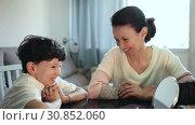 Купить «Cheerful woman telling funny story to her teenage son at home table», видеоролик № 30852060, снято 26 апреля 2019 г. (c) Яков Филимонов / Фотобанк Лори