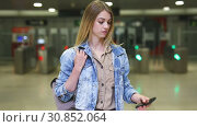 Купить «Young woman traveler looking at itinerary map at metro station», видеоролик № 30852064, снято 25 апреля 2019 г. (c) Яков Филимонов / Фотобанк Лори