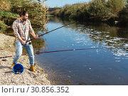 Купить «Adult man standing near river and pulling fish expressing emotions of dedication», фото № 30856352, снято 15 марта 2019 г. (c) Яков Филимонов / Фотобанк Лори