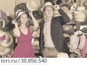 Купить «attractive young female and man choosing hats in the store», фото № 30856540, снято 2 мая 2017 г. (c) Яков Филимонов / Фотобанк Лори