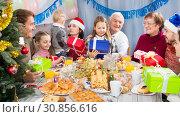 Купить «Large family handing gifts to each other», фото № 30856616, снято 26 июня 2019 г. (c) Яков Филимонов / Фотобанк Лори
