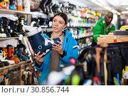 Купить «Female looking for new ski boots in shop», фото № 30856744, снято 16 апреля 2019 г. (c) Яков Филимонов / Фотобанк Лори