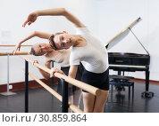 Купить «Choreographer woman and young man do exercises at ballet bar in hall with mirror», фото № 30859864, снято 26 апреля 2019 г. (c) Яков Филимонов / Фотобанк Лори