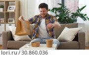 Купить «man unpacking and eating takeaway food at home», видеоролик № 30860036, снято 24 мая 2019 г. (c) Syda Productions / Фотобанк Лори