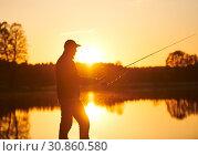 Купить «sunset fishing. fisher with spinning rod», фото № 30860580, снято 8 мая 2019 г. (c) Дмитрий Калиновский / Фотобанк Лори