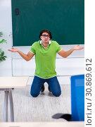 Купить «Young male student in front of green board», фото № 30869612, снято 26 февраля 2019 г. (c) Elnur / Фотобанк Лори