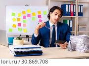 Купить «Young businessman working in the office», фото № 30869708, снято 28 декабря 2018 г. (c) Elnur / Фотобанк Лори