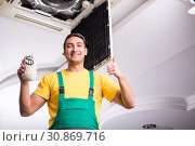 Купить «Young repairman repairing ceiling air conditioning unit», фото № 30869716, снято 27 февраля 2019 г. (c) Elnur / Фотобанк Лори