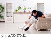 Купить «Leg injured young man suffering at home», фото № 30870224, снято 15 января 2019 г. (c) Elnur / Фотобанк Лори