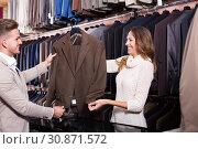 Купить «Smiling couple examining various suits», фото № 30871572, снято 19 июля 2019 г. (c) Яков Филимонов / Фотобанк Лори