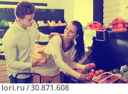 Купить «Couple choosing fruits in shop», фото № 30871608, снято 23 ноября 2016 г. (c) Яков Филимонов / Фотобанк Лори