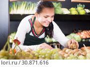 Купить «Woman seller placing kiwis», фото № 30871616, снято 23 ноября 2016 г. (c) Яков Филимонов / Фотобанк Лори