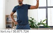 Купить «indian man exercising and leaning at home», видеоролик № 30871724, снято 27 мая 2019 г. (c) Syda Productions / Фотобанк Лори