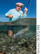 Купить «Saltwater fly fishing Over/under off man hold a BIG BONEFISH underwater saltwater fly fishing los roques venezuela.», фото № 30872996, снято 30 апреля 2019 г. (c) age Fotostock / Фотобанк Лори