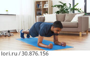 Купить «man with fitness tracker doing plank at home», видеоролик № 30876156, снято 27 мая 2019 г. (c) Syda Productions / Фотобанк Лори