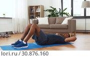 Купить «indian man making abdominal exercises at home», видеоролик № 30876160, снято 27 мая 2019 г. (c) Syda Productions / Фотобанк Лори