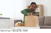 Купить «indian man with takeaway coffee and food at home», видеоролик № 30876164, снято 27 мая 2019 г. (c) Syda Productions / Фотобанк Лори