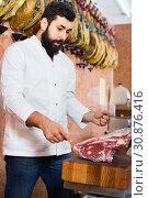 Купить «Man seller grouping meat to sell in butcher's shop», фото № 30876416, снято 16 ноября 2016 г. (c) Яков Филимонов / Фотобанк Лори