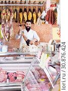 Купить «Male shop assistant demonstrating jamon», фото № 30876424, снято 16 ноября 2016 г. (c) Яков Филимонов / Фотобанк Лори