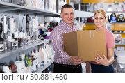 Купить «Young family holding packed new purchases in appliances store», фото № 30881480, снято 1 марта 2018 г. (c) Яков Филимонов / Фотобанк Лори