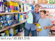 Купить «Family of father and son looking household chemicals with shopping list», фото № 30881516, снято 4 июня 2018 г. (c) Яков Филимонов / Фотобанк Лори