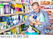 Купить «Man looking at shopping list of household detergents», фото № 30881520, снято 4 июня 2018 г. (c) Яков Филимонов / Фотобанк Лори