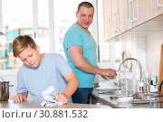 Купить «Smiling bou is washing dishes with his father together», фото № 30881532, снято 25 июня 2018 г. (c) Яков Филимонов / Фотобанк Лори