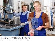 Купить «Female worker demonstrating drilled glass», фото № 30881740, снято 10 сентября 2018 г. (c) Яков Филимонов / Фотобанк Лори