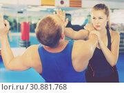 Купить «Woman is training with man on the self-defense course in gym.», фото № 30881768, снято 21 августа 2017 г. (c) Яков Филимонов / Фотобанк Лори