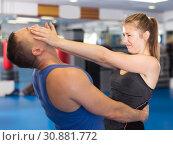 Купить «Cheerful woman is fighting with trainer», фото № 30881772, снято 21 августа 2017 г. (c) Яков Филимонов / Фотобанк Лори