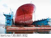 Купить «Huge red tanker is under repairing», фото № 30881932, снято 16 июля 2014 г. (c) EugeneSergeev / Фотобанк Лори