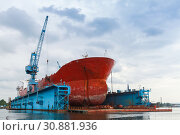 Купить «Red tanker is under repairing», фото № 30881936, снято 16 июля 2014 г. (c) EugeneSergeev / Фотобанк Лори