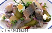 Купить «Slices of mild-cured herring with potatoes and onions served on white plate», видеоролик № 30888624, снято 27 августа 2018 г. (c) Яков Филимонов / Фотобанк Лори