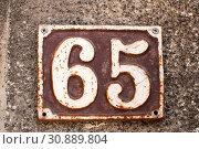 Купить «Old retro weathered cast iron plate with number 65», фото № 30889804, снято 10 апреля 2020 г. (c) easy Fotostock / Фотобанк Лори