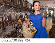 Купить «adult female choosing natural dried herbs sold by weight in eco shop», фото № 30892724, снято 13 июня 2017 г. (c) Яков Филимонов / Фотобанк Лори