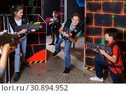 Купить «Cheery teens aiming laser guns at other players», фото № 30894952, снято 24 октября 2018 г. (c) Яков Филимонов / Фотобанк Лори
