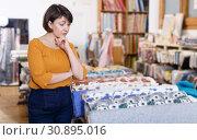 Купить «Pensive female customer in cloth store», фото № 30895016, снято 7 февраля 2019 г. (c) Яков Филимонов / Фотобанк Лори