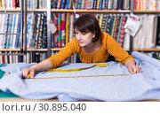 Купить «Saleswoman measuring and cutting off piece of cloth», фото № 30895040, снято 7 февраля 2019 г. (c) Яков Филимонов / Фотобанк Лори