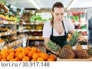 Купить «Young woman wearing apron working with fresh pineapples», фото № 30917148, снято 27 апреля 2019 г. (c) Яков Филимонов / Фотобанк Лори