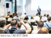 Купить «Male business speaker giving a talk at business conference event. Rear view of unrecognized participant in audience taking photo of presentation.», фото № 30917564, снято 15 июня 2018 г. (c) Matej Kastelic / Фотобанк Лори
