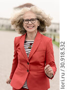 Vital senior woman (67 years old) running outdoors in city, in Munich, Germany. Стоковое фото, фотограф Benjamin Egerland / age Fotostock / Фотобанк Лори