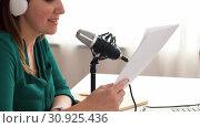 Купить «woman with microphone recording podcast at studio», видеоролик № 30925436, снято 4 апреля 2020 г. (c) Syda Productions / Фотобанк Лори