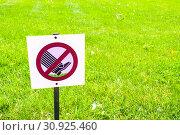 Купить «The prohibitive sign on the label Do not walk the lawn - closeup against tha lawn in sunlight», фото № 30925460, снято 6 июня 2019 г. (c) Зезелина Марина / Фотобанк Лори