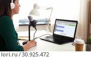 Купить «woman with microphone recording podcast at studio», видеоролик № 30925472, снято 19 февраля 2020 г. (c) Syda Productions / Фотобанк Лори